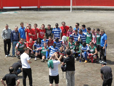 The teams line up together in front of the cameras after the match